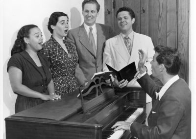 Leonard Bernstein at piano, rehearses with singers Adele Addison, Eunice Alberts, James Pease, and David Lloyd, Photograph by Heinz Weissenstein, Whitestone Photo