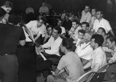 Leonard Bernstein (at piano) surrounded by a class of auditors, analyzes his Age of Anxiety, circa August 1949. Photograph by Howard Babbitt