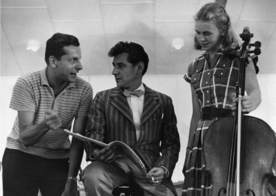 Leonard Bernstein discusses a score with TMC student conductor Stefan Bauer-Mengelberg and TMC cellist Joanna Noble, circa 1955. Photograph by Walter Alford